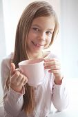 image of 7-year-old  - 7 years old girl drinking hot cocoa from the big pink cup - JPG