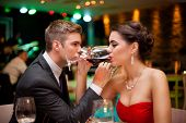 Romantic couple drinking wine with crossed arms