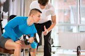 Man doing weights lifting exercise under supervision an instructor