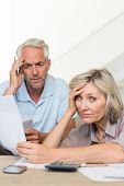 Tensed mature man and woman with bills sitting on sofa at home