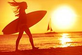 Surfing surfer woman babe beach fun at sunset. Girl walking in sunshine in warm evening sun holding