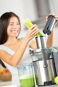 Vegetable juice - woman juicing green vegetables on juicer machine or juice maker. Healthy raw food concept with person making celery vegetable juice in kitchen. Focus on celery.