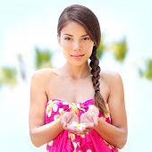 Spa wellness pretty tanned woman portrait. Mixed race asian caucasian female model looking relaxed in zen meditation at camera - flower in hand. Big Island, Hawaii, USA