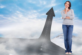 picture of thinkers pose  - Young woman in thinkers pose against road turning into arrow - JPG