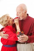 Romantic senior couple feeds each other healthy berries.  White background