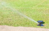 pic of underground water  - Round shape water sprinkler system watering on fresh green grass near concrete road - JPG