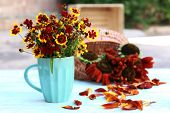 Beautiful sunflowers in vase on wooden table, outdoors