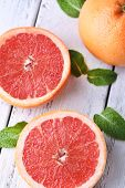 Ripe grapefruits on color wooden background