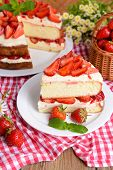 Delicious biscuit cake with strawberries on table on brown background