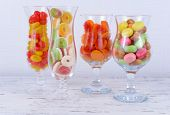 Different colorful fruit candy in glasses on table on light background
