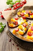 Tasty bruschetta with tomatoes on pan, on old wooden table