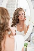 Young Beautiful Woman Admires Her Reflection In The Mirror