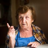 Emotional old woman sitting at table in his house. Close-up.