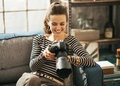 Happy Young Woman Sitting On Divan And Using Modern Dslr Photo Camera