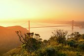 Golden Gate Bridge sunrise viewed from mountain top with San Francisco downtown