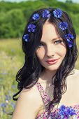 beautiful young girl with long black hair with a wreath of cornflowers with makeup walking