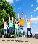 Group Of Smiling Teenagers Jumping Outdoors
