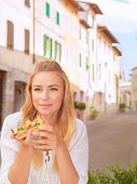 Portrait of beautiful woman eating pizza outdoors in the restaurant in Italy, traditional Italian me