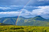 Summer landscape with a rainbow in the mountains. Sunshine after the rain. Beauty in nature