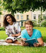 Multi ethnic students couple preparing for final exams in a city park