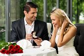 stock photo of love making  - Man holding box with ring making propose to his girlfriend - JPG