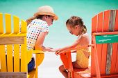 Mother talking to upset little daughter while sitting on colorful wooden chairs at tropical beach during summer vacation