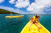 Family with kids paddling on colorful yellow kayaks at tropical ocean water during summer vacation