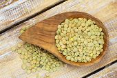 Green lentils in wooden bowl on wooden surface