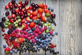 Summer wild berry fruits on vintage board