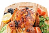baked meat : fresh whole chicken with black olives and raw tomatoes on wooden board isolated over wh