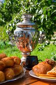 Samovar On A Wooden Table With Cakes  Candies And Berries