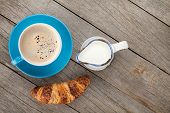 Cup of coffee, milk and fresh croissant on wooden table