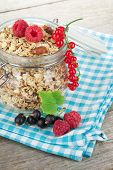 Healty breakfast with muesli and berries. On wooden table