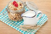 Healty breakfast with muesli, berries and milk. On wooden table