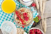 Healty breakfast with muesli, berries and orange juice. On wooden table