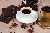 sweet hot drink : black Turkish coffee in small white mug with coffee beans spilled on a wooden tabl