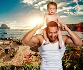 Loving Father With Daughter On Shoulders Against Beach Background