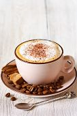 picture of cinnamon  - Cup of fresh cappuccino coffee with coffee beans brownsugar and cinnamon sticks close-up.