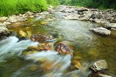 mountain river flowing over rocks in summer - long exposure