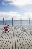 View of horizon over water with baby stroller on wooden dock