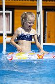 Little blonde girl in swimming pool