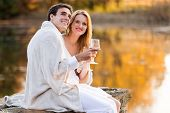 lovely young couple having wine by the lake at sunset