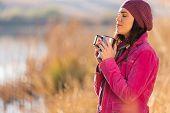 beautiful woman enjoying winter morning outdoors by the lake