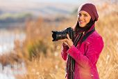 beautiful young woman holding a dslr camera outdoors in autumn