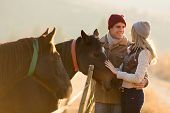 lovely young couple petting a horse in a paddock