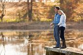 pic of snuggle  - lovely young couple fishing together by a lake - JPG