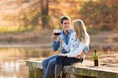 cheerful couple enjoying glass of red wine by the pond