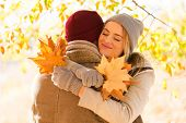 beautiful young woman hugging her boyfriend in fall