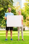 fitness, sport, friendship and lifestyle concept - smiling couple with big white blank billboard out