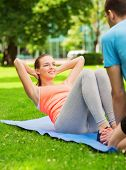 fitness, sport, training, park and lifestyle concept - smiling woman with personal trainer doing exe